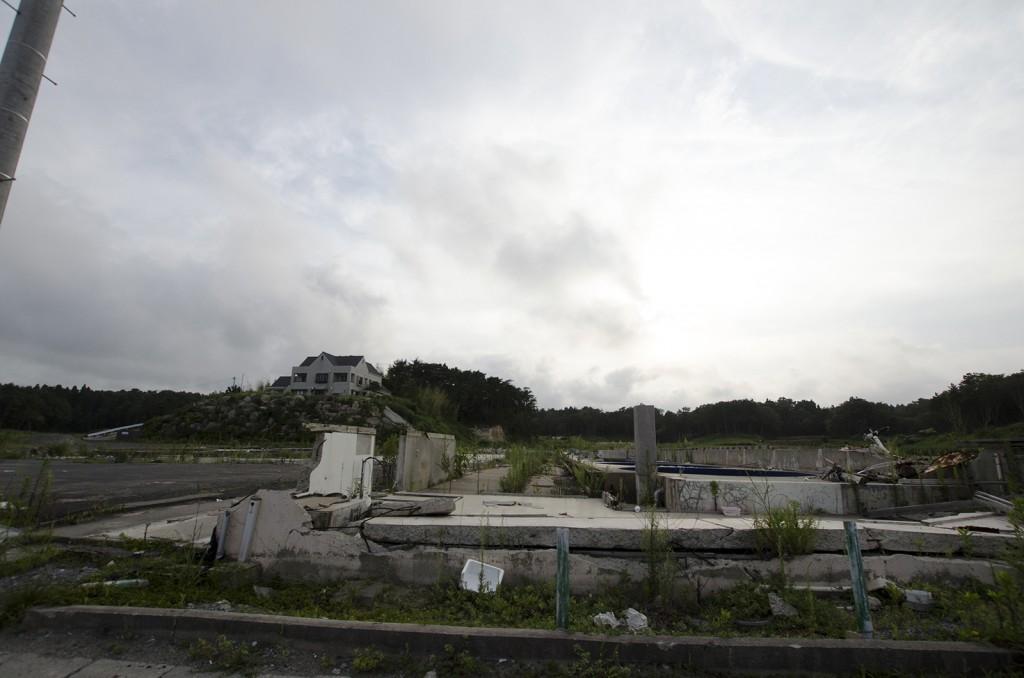 手前は工場の残骸。奥の家はその工場の社長宅。高台にあるが、一階部分にも津波がきたそうだ。